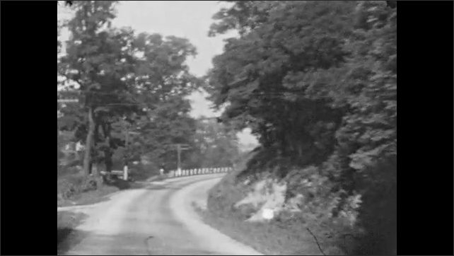 1930s: Driving around bends down rural road.