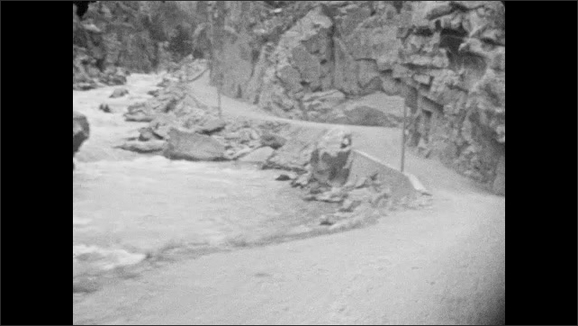 1930s: Car drives along narrow road with rock barrier and approaches tunnel through rock. Car drives on road alongside river. Car drives through rock tunnel and meets another car coming towards it.