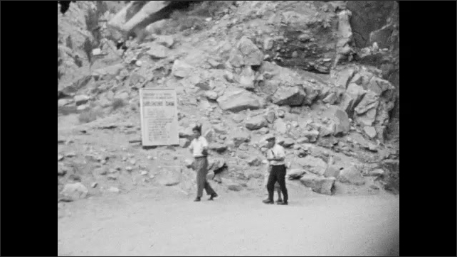 1930's: Car drives up steep dirt road to sign reading Shoshone Dam. Car drives through a tunnel. Pedestrians walk on road.