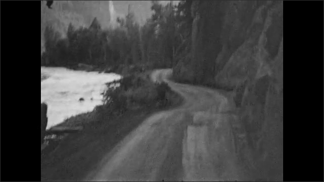 1930s: Car drives on dirt road surrounded by trees amongst mountains.