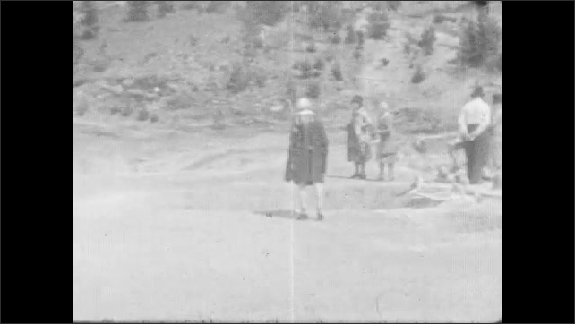 1930s: Young bear stands on his hind legs at side of road. Young bear approaches car and eats food off car. Woman and young girl walk. Sign for Mud Volcano, Dragons Mouth. Tourists walk on boardwalk.