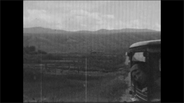 1930s: Road. Fence along roadside, mountains. Woman looks out car window. River.