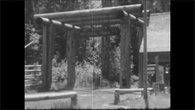 1930s: Car drives along dirt road through forest. Sign for Mt. Rainier national park. Girl runs underneath sign.