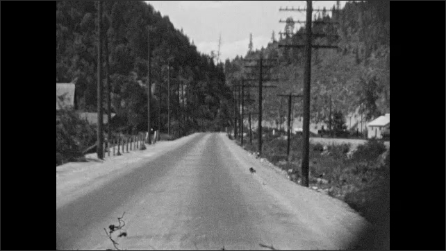 1930s: Sign for Yellowstone Trail Garage. Man walks down street in town. Car drives down road. Highway 10 Idaho sign. Railroad tracks.