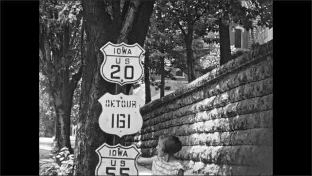 1930s: Road signs for Iowa US 20, Detour 161 and Iowa US 55, highways. Girl walks up, stands next to signs, then points at them.