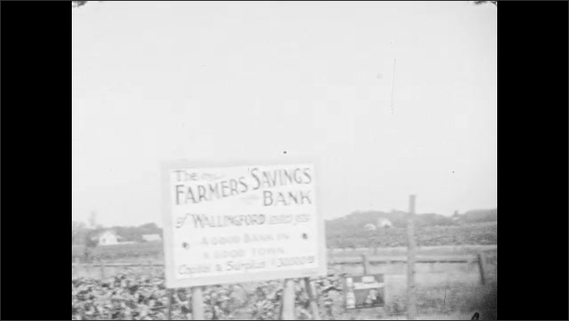 1930s: Driving down road behind traffic. Sings for service station. Field of farm crops. Woman and girl sitting in parked car.
