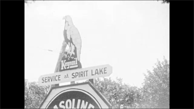 1930s: Trees. Looking down rural road. Sign for service station. Girl runs through bushes. Girl dips stick into lake.