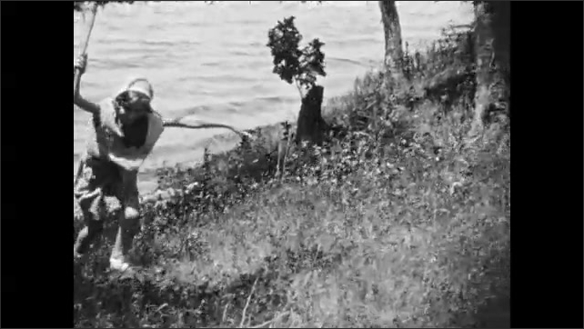 1930s: Girl runs up hill on side of lake, holding tree branch. Girl runs towards parked car.