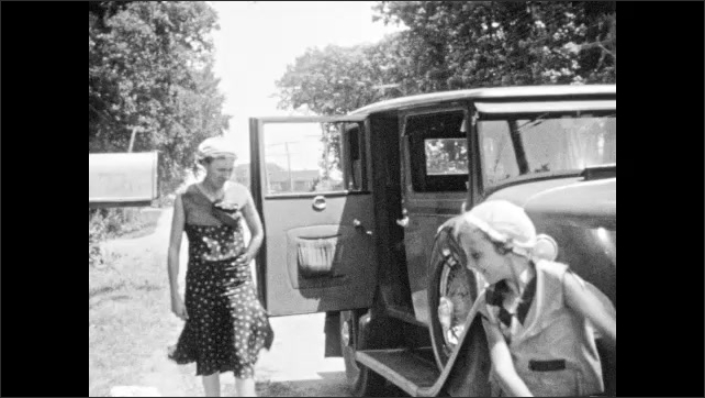 1930s: Woman and girl stand by parked car, with door open. Girl dances around. Girl holds doll while running around in circle.
