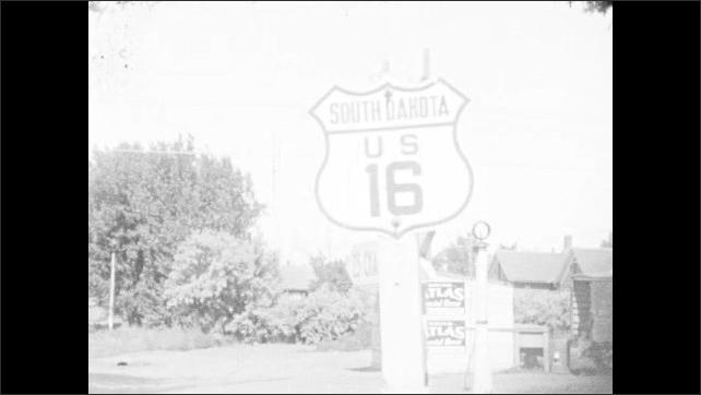 1930s: Title card: Along Custer Battlefield Highway. Sign for Highway. Road sign for stops along Highway 16. Sign for South Dakota Highway 16. Title card: Emery, South Dakota. City street. Road.
