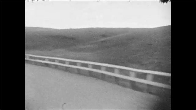 1930s: Car drives along curving roads in hilly terrain.