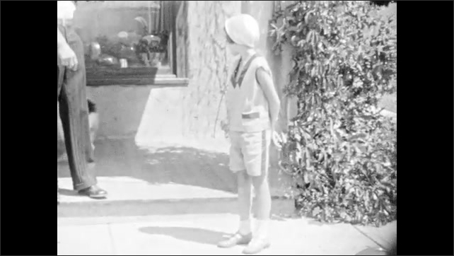 1930s: Title card. Dog runs from porch Girl watches dog on porch. Dog runs around girl. Girl pets dog.