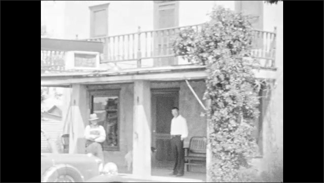 1930s: Title card. Small hotel. Men and dog stand on porch of hotel near parked car. Cars parked along small western town.