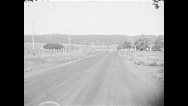 1930s: Wooden road sign. Car drives along rural dirt road lined with electric poles. Car drives past fields of cattle in rural terrain. Car drives along curving roads in hilly terrain.