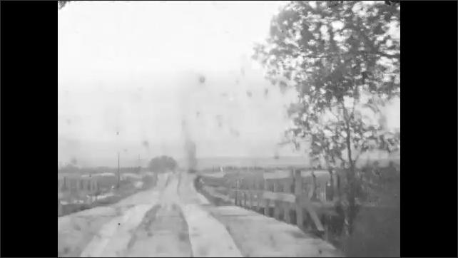 1930s: Car drives along muddy dirt road in rural terrain. Car passes over wooden bridge. Car passes man walking on dirt road.