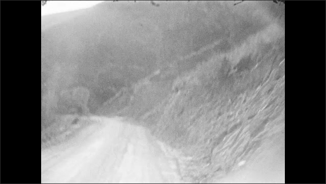 1930s: Car drives down curvy mountain road.