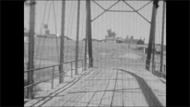 1930s: Car drives over tall metal bridge. Car drives along curving dirt roads in hilly terrain.