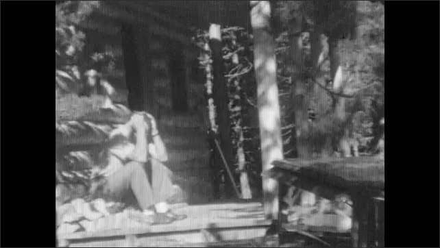 1930s: Hand tickles cat with blade of grass. Man exits cabin doorway and sits on porch. Man stands and leans on porch post. Girl exits cabin and stands near man.