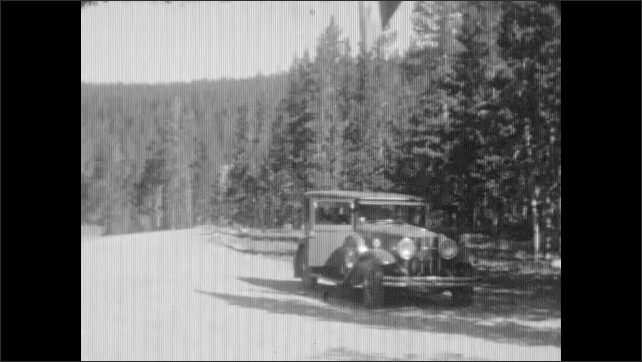 1930s: Car drives down heavily forested road with wooden handrails. Car parked on the side of the dirt road. Pile of deer or caribou antlers.