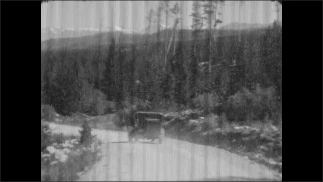 1930's: Car drives down single-lane dirt road towards mountains and through pine forest following another car. Trees are down on the side of the road.