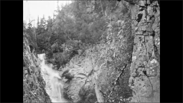 1930s: Group of people stand in front of waterfall. Group stands along hillside, by waterfall.