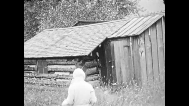 1930s: Girl in garden. Log cabin. Woman approaches cabin, picks up something from ground and holds it up.