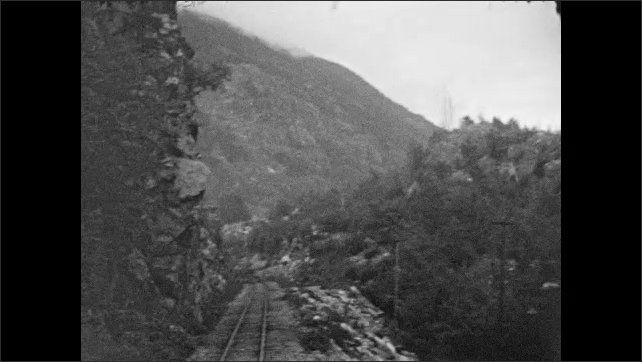 1930s: View of mountains from rear of train. Train goes down tracks.