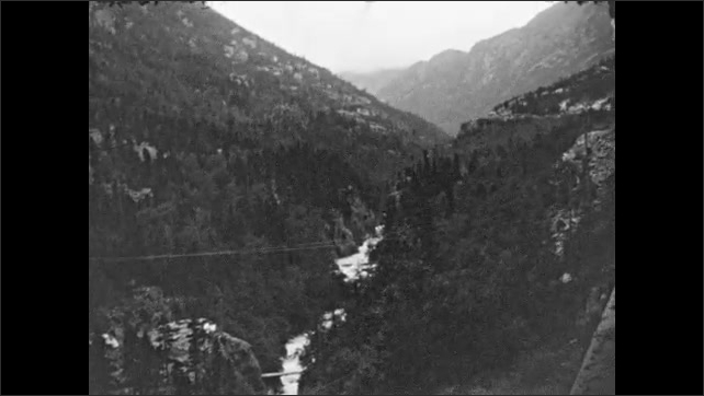1930s: View of mountains from rear of train. River runs through valley in mountains. River flows.