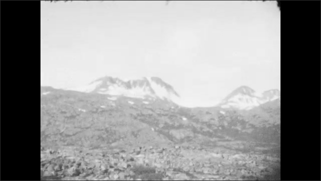 1930s: ALASKA: mountain top and scree seen from train window. Snow on mountains. Rocks by tracks