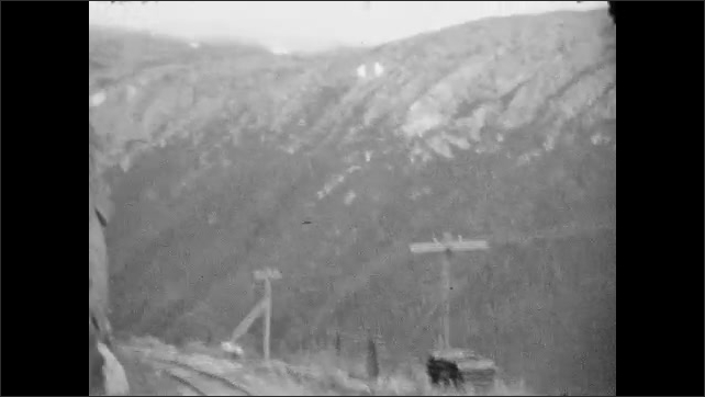 1930s: ALASKA: workers on railway tracks in mountains. Train crosses wooden bridge, View along side of train from carriage window
