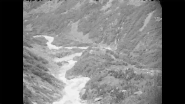 1930s: ALASKA: river runs down mountain slope. River cuts through gorge. Tutshi sign on boat.