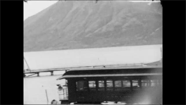 1930s: ALASKA: wooden bridge above water. Bridges across water. M.Watson General Store sign