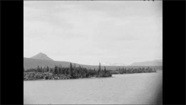 1930s: ALASKA: Mountains next to water. View towards mountains on horizon. Trees by edge of water
