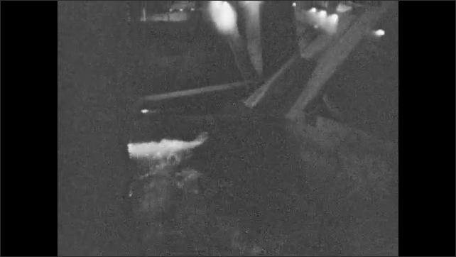 1930s: ALASKA: barrel empties contents inside mill. Water flows through mill. Interior of wood mill