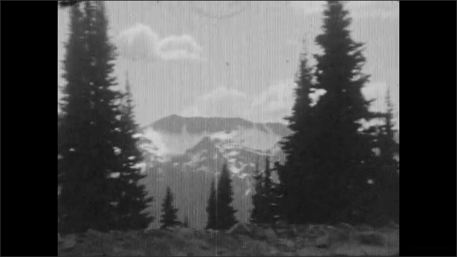 1930s: Young woman wears swim cap, swims and smiles, sun shines on water. Trees, Glacier Peak in background, car drives on dirt road. Mountain peak with snow, tree on the right.
