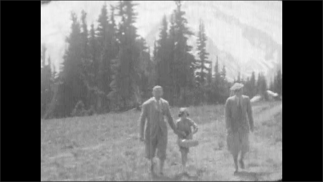 1930s: Crowd of people stand next to parked cars on a mountain and look. Man holds hands with girl, they hike on a trail, people pass by, mountain with snow in background.