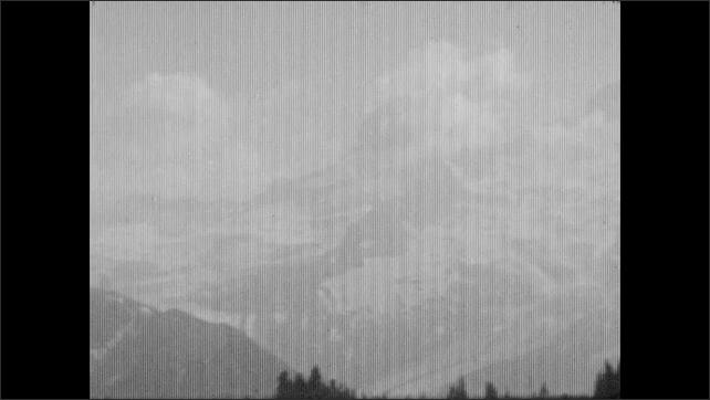 1930s: ALASKA: girl runs across grass slope. View across mountains. Snow patch on mountain top
