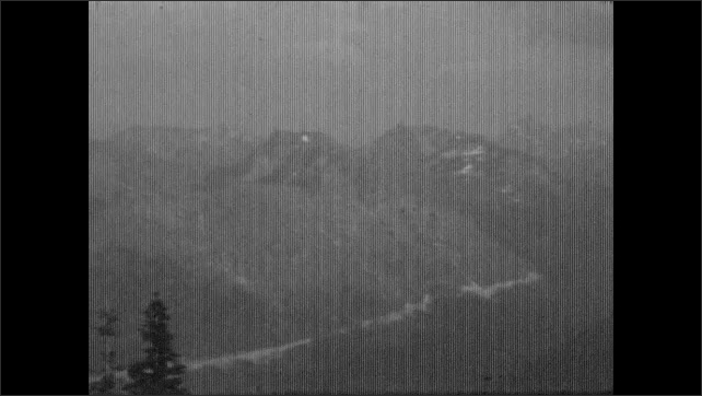 1930s: ALASKA: view across mountain tops. Trees in valley. Track through mountains. Girl plays in sand on beach.