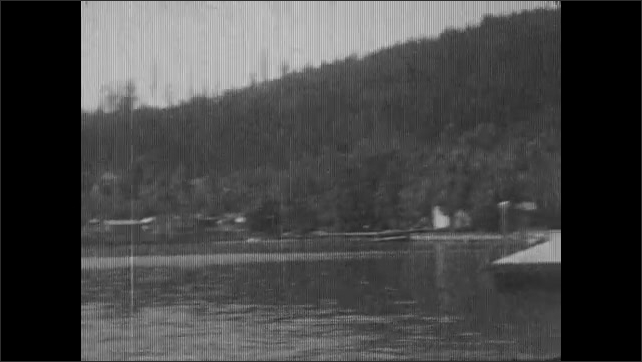 1930s: ALASKA: children paddle in water. Children play in water. View across lake. Hut by beach. Lady lies in sun