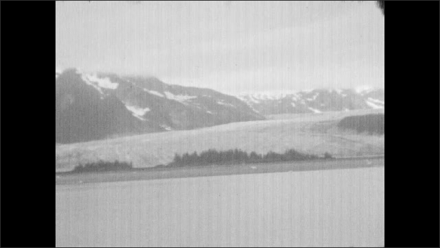 1930s: ALASKA: snow covered mountains in distance. View across water. Spit of land. Glacier meets water