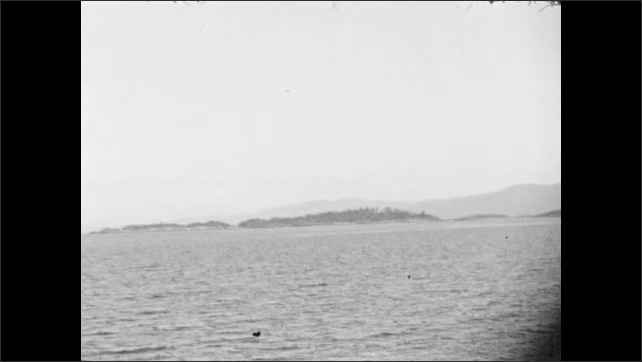 1930s: ALASKA: ship on water. Island seen from boat. Land by water
