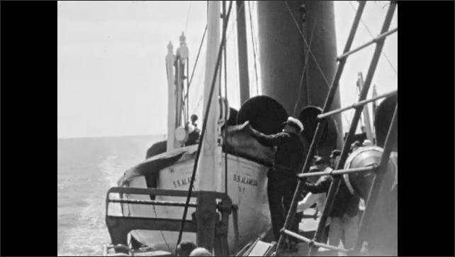 1930s: ALASKA: captain on deck of ship. Men launch boats from deck of ship