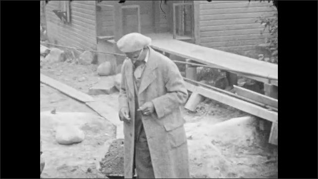 1930s: ALASKA: man helps passengers down from boat. Man shovels sand into wheelbarrow