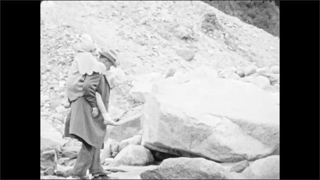 1930s: ALASKA: man gives child piggyback across glacier.
