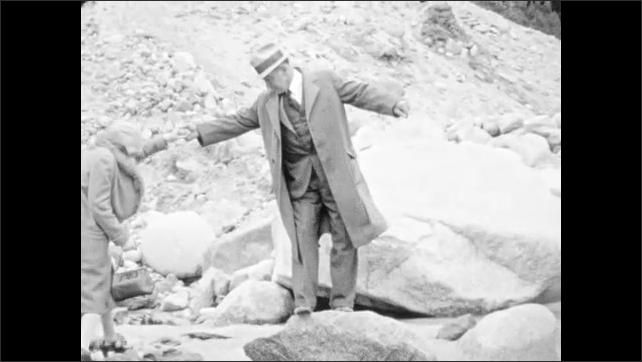 1930s: ALASKA: man helps lady across rocks. Lady in heels crosses river rocks. Girl waits for parents