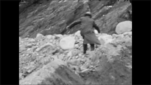 1930s: Man on hilltop, next to giant boulder. Man kneels along edge of rocky ravine. Snow on hillside, through tree line.