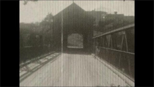 1940s: Cars travel down dirt road in the country, crosses covered bridge.