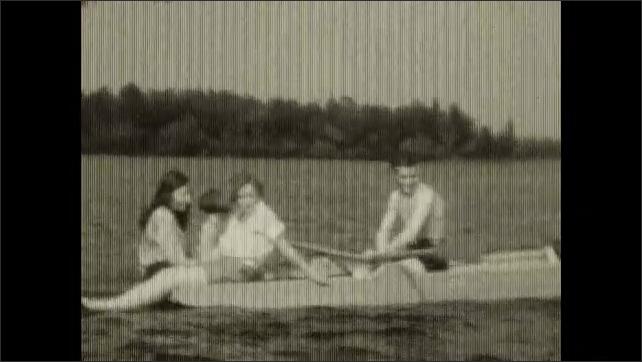 1930s: Trcking shot, people on boat, man rowing. Views of women sitting on boat. Man rowinf boat with women.