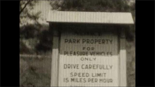 1930s: Man closes car door. Man poses next to car. View of sign. View of guard rail, trees.