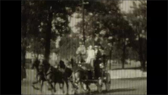 1930s: Carriage drives past camera. Carriage drives past fence.